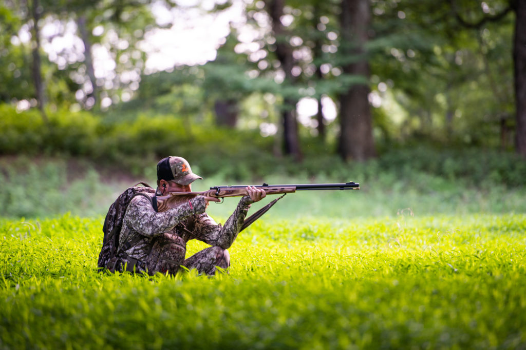 Middle-aged man squatting in a field holding a muzzleloader after completing his hunting gear checklist